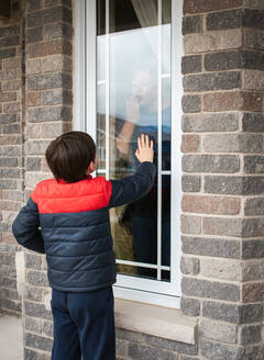 Young boy looking through window at grandma during Covid 19 pandemic. - CAVF83075