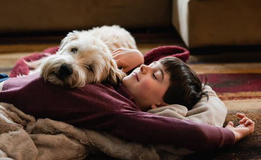 Boy and his dog cuddling on the floor together on a blanket. - CAVF83087