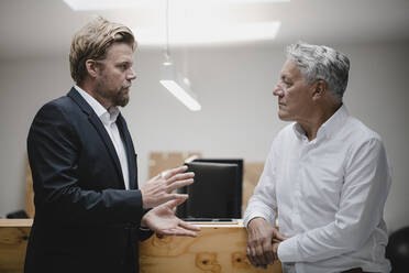 Business partners standing in office, talking - GUSF03821