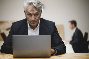 Senior businessman working on laptop, sitting in office with collueague - GUSF03845