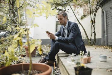 Businessman sitting in backyard, using smartphone while gardening - GUSF03851