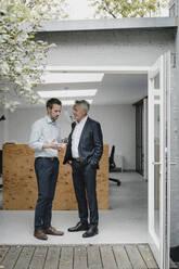 Two businessmaen standing in open office door, talking - GUSF03857