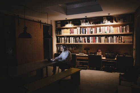 Senior businessman sitting in office, working late - GUSF03914