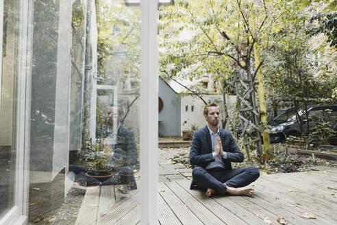 Businessman practicing yoga in backyard - GUSF03926