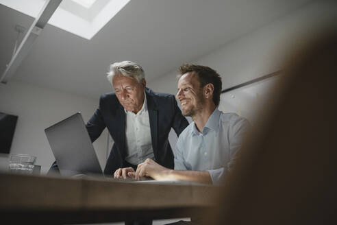 Senior businessman supporting younger colleague in office - GUSF03938
