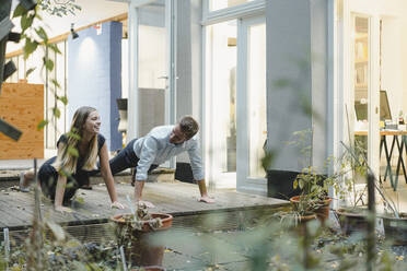 Businessman and woman taking a break, practicing pushups in backyard of loft office - GUSF03953