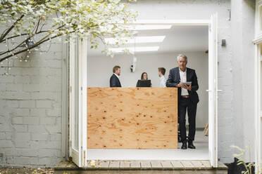 Senior businessman standing in office, using digital tablet, people working in background - GUSF03995