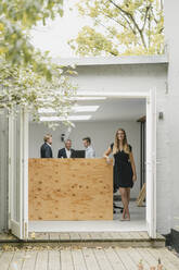 Businesswoman standing in open office door, people working in background - GUSF03998