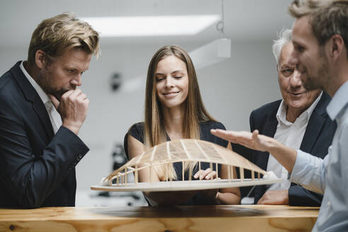 Successful business people looking at architectural model in office - GUSF04001