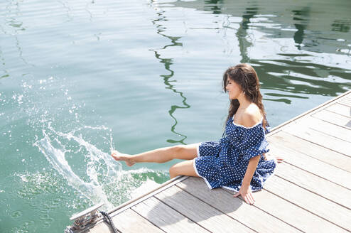 Young woman splashing water in sea with legs while sitting on jetty - DIGF12458