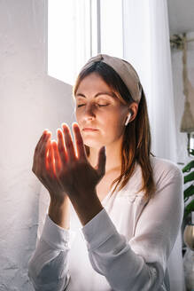 Beautiful woman praying with eyes closed by window at home - ERRF03855