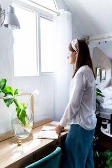 Woman looking through window while standing at desk in bedroom - ERRF03873