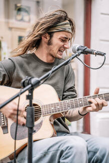 Young rocker with long hair and a headband playing guitar in front of a microphone - CAVF83374