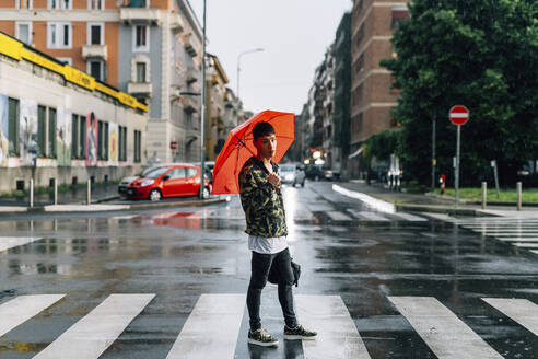 Young man with umbrella standing on street in city during rainy season - MEUF00616