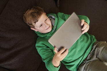 Smiling boy using digital tablet while lying on sofa at home - MMIF00274