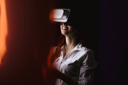 Young woman smiling while using VR glasses over black background - LJF01535