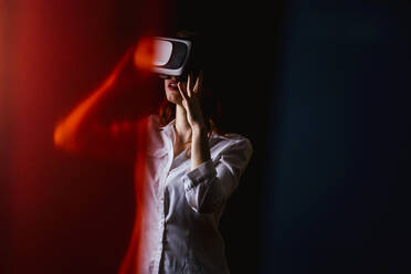 Young woman using VR glasses over black background - LJF01538