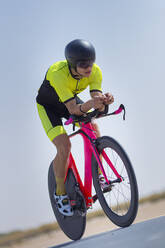 Confident cyclist riding bicycle on road against clear blue sky at desert in Dubai, United Arab Emirates - SNF00237