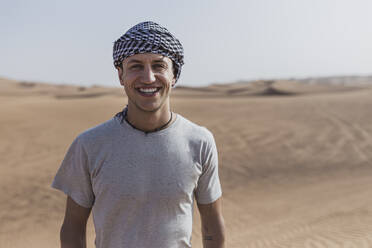 Happy young man standing at desert in Dubai, United Arab Emirates - SNF00243