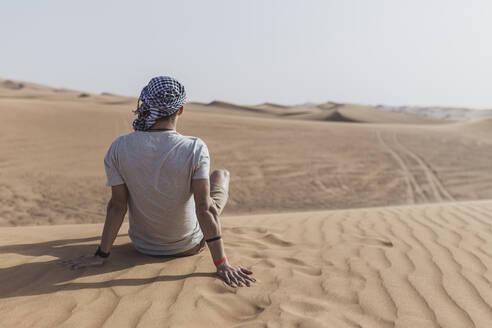 Young man sitting on sand dunes in desert at Dubai, United Arab Emirates - SNF00246