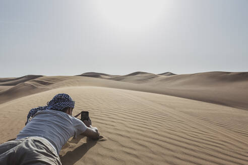 Male tourist taking picture through smart phone while lying on sand dune at desert in Dubai, United Arab Emirates - SNF00249