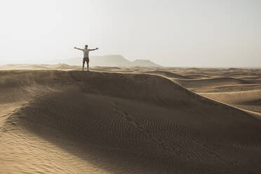 Mid distance of male tourist standing with arms outstretched on sand dunes in desert at Dubai, United Arab Emirates - SNF00255
