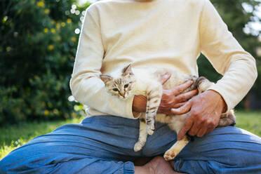 Senior man cuddling with his cat in garden - AFVF06397