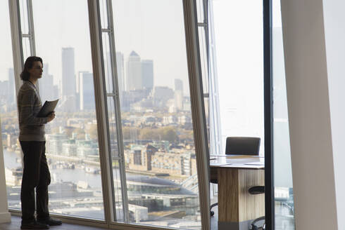 Thoughtful businessman standing at urban highrise office window - CAIF27546