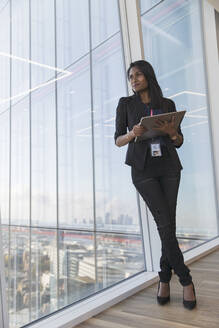 Confident businesswoman with digital tablet at highrise office window - CAIF27585