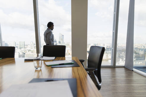 Thoughtful businessman looking at cityscape at conference room window - CAIF27591