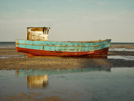 Abandoned fishing boat moored on shore at beach against sky - VEGF02317