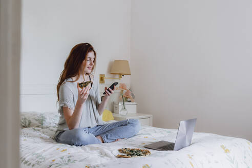 Beautiful woman using mobile phone while sitting with pizza and laptop on bed at home - AFVF06412