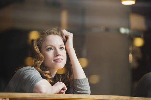 Thoughtful woman leaning on table seen through glass window in coffee shop - DIGF12471
