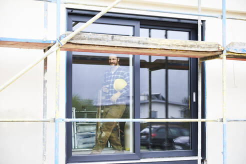 Worker standing behind window on a construction site - MJFKF00251