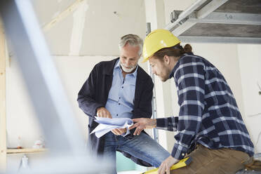 Architect and worker discussing building plan on a construction site - MJFKF00275