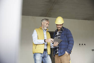 Architect and worker sharing tablet on a construction site - MJFKF00287