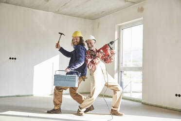 Smiling construction workers with drill and tool box at construction site - MJFKF00299