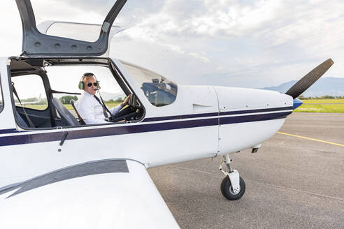 Pilot with headset, sitting in sports plane - WPEF02952