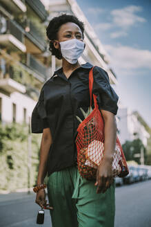 Portrait of young woman wearing protective mask standing on street with her purchase - MFF05832