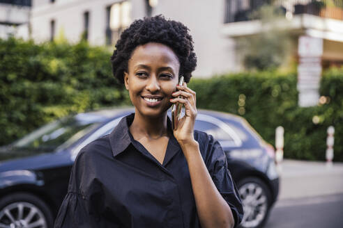 Portrait of smiling young woman on the phone outdoors - MFF05838