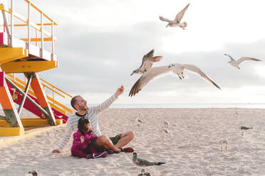 Father feeding seagulls while sitting with daughter at Miami beach, Florida, USA - GEMF03796