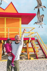 Happy father carrying daughter feeding seagulls while standing at Miami beach, Florida, USA - GEMF03799