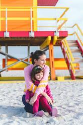 Smiling mother embracing daughter at Miami beach against lifeguard hut, Florida, USA - GEMF03802