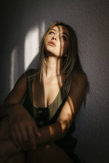 Seductive young woman looking away while leaning on wall at home - TCEF00721