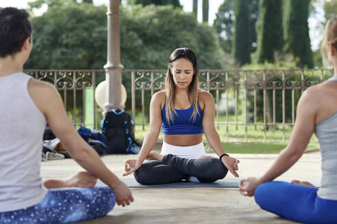 Yoga instructor practicing lotus position with man and woman in gazebo at Ciutadella Park - JNDF00153