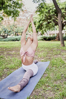 Mid adult woman practising yoga on mat in park - JNDF00156