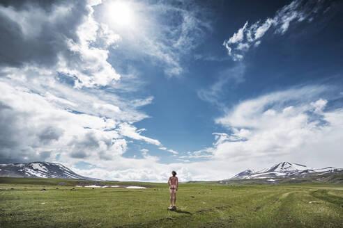 Georgia, Samtskhe-Javakheti, Male nudist standing in grassy plateau under shining sun - WVF01694