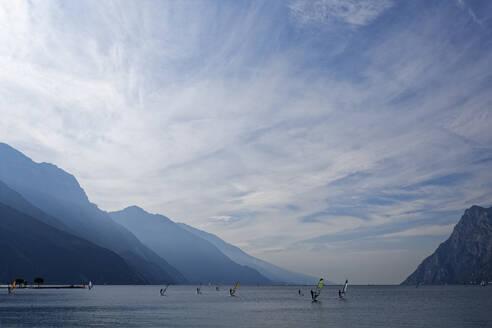 Italy, Trentino, Torbole, Windsurfers on Lake Garda surrounded with mountains  - UMF00942