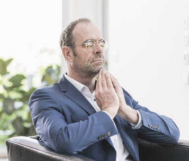 Portrait of businessman wearing glasses sitting in armchair meditating with eyes closed - UUF20392