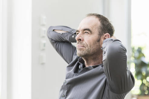 Portrait of pensive mature man with hands behinds his head looking at distance - UUF20398